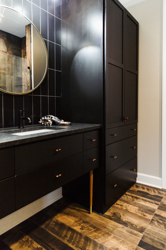 bathroom with black vanity and stone countertops