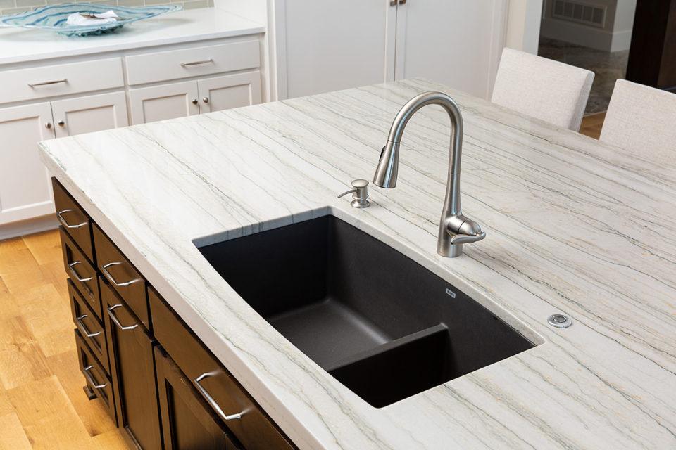 kitchen island with a black under mount sink