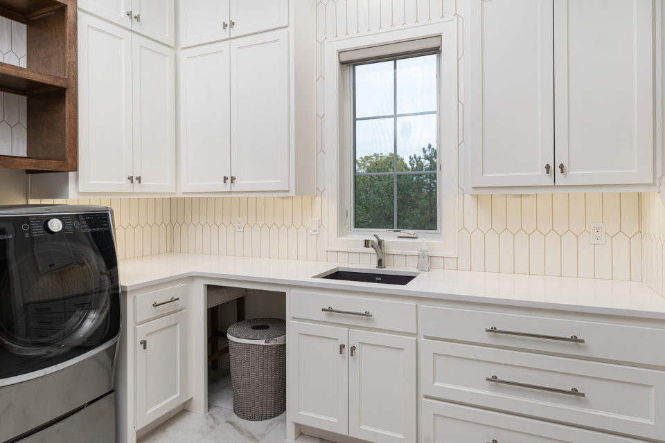 Laundry room with white quartz countertops and tiles