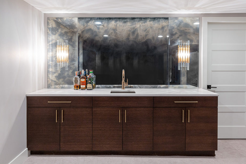 bar with wood cabinetry and stone