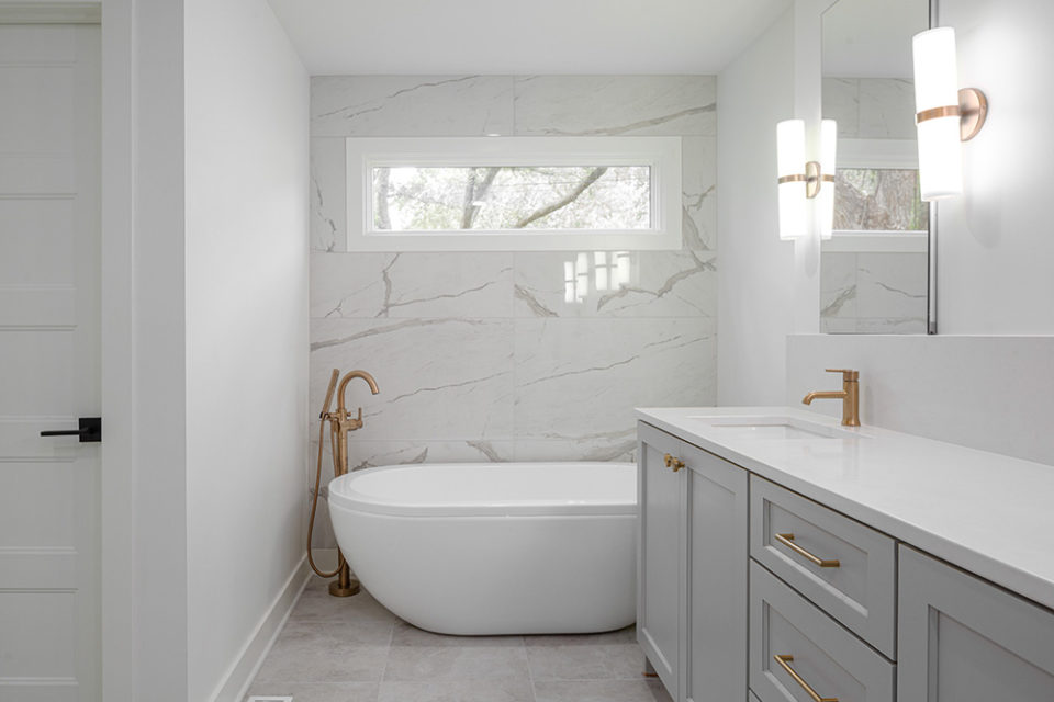 bathroom with white soaker tub and grey marble wall