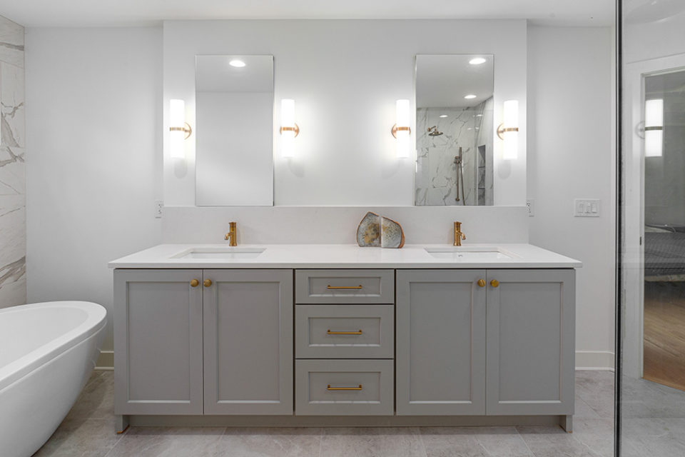 bathroom with white stone his and her vanity and gray cabinets